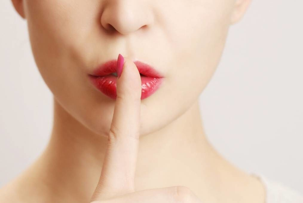 Infidelity, adultery and secrets. Woman holding finger in front of mouth to indicate secret.