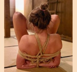 Kinbaku Shibari Elisabet Barnes on floor with hands bound