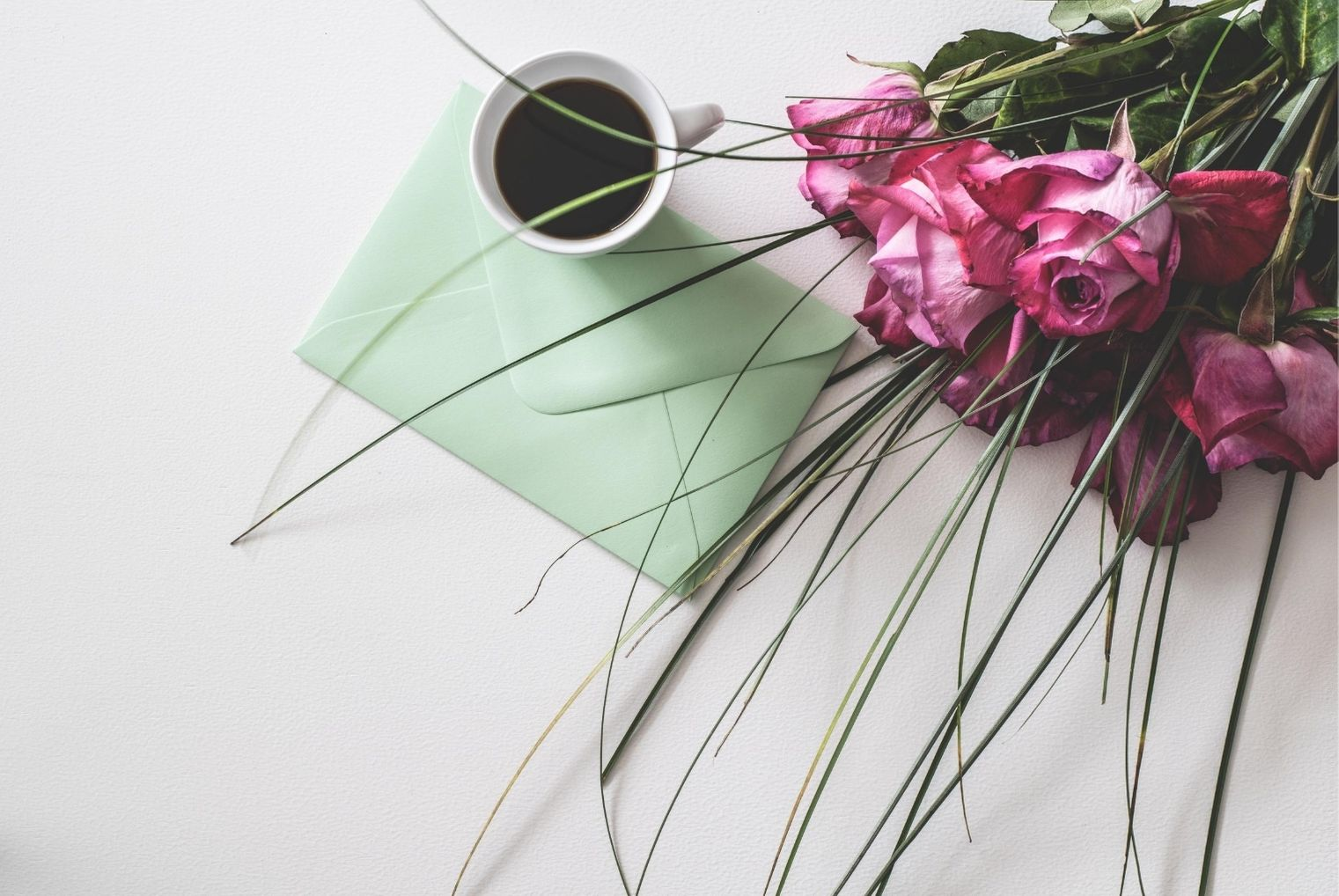 Flowers and envelope with coffee mug, receiving gifts