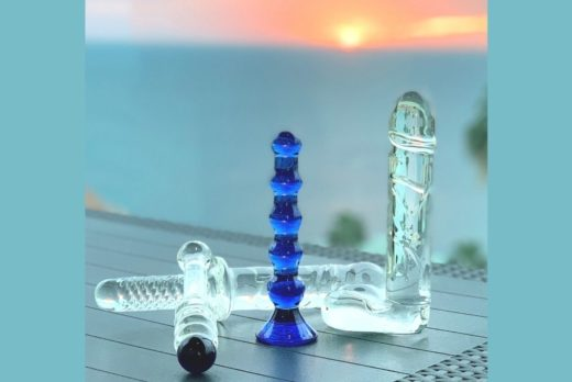 four glass dildos on table in sunset. Toy Tuesday blog image Elisabet Barnes