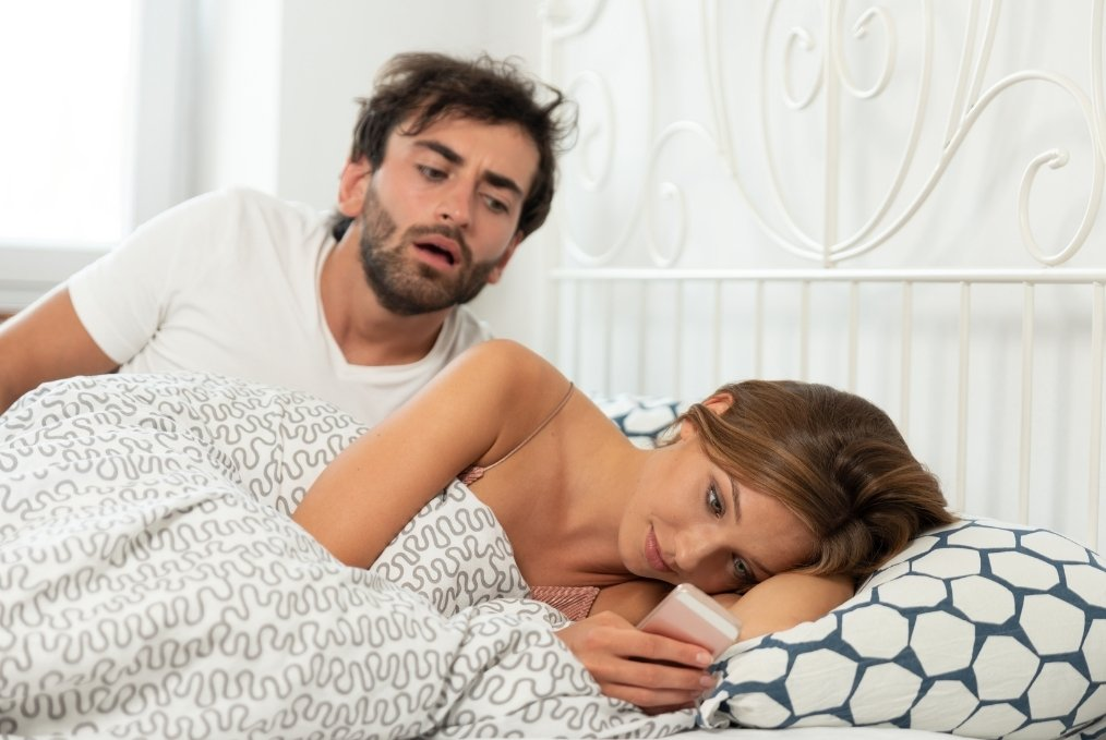 Jealous man looking at partner's phone in bed. Jealously.